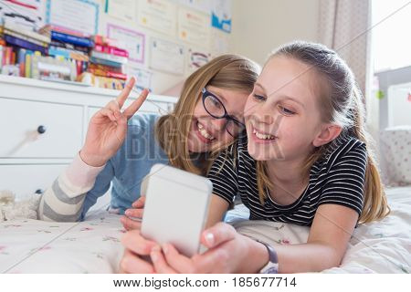 Two Young Girls Posing For Selfie In Bedroom