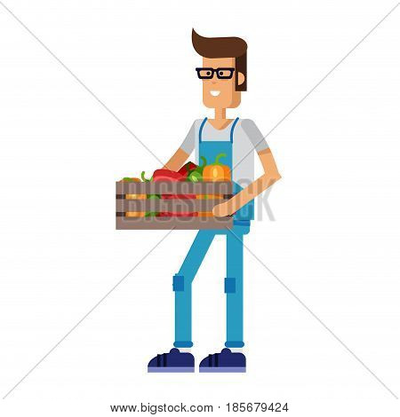Young farmer in overalls holding a basket with vegetables and shows the side isolated on white background. Supplier of organic products.