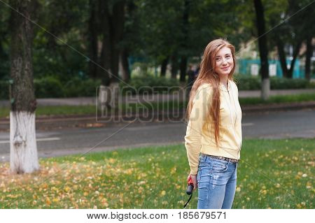 A pretty girl with long red hair, walks through the park and smiles. Portrait in the open air