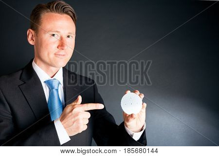 a businessman is holding a silicon wafer with semiconductor structures on it.