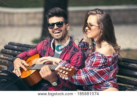 Happy Couple at the Park Playing Guitar and Singing Songs.