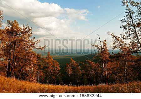 Autumn mountain aerial view from the top of Sugomak mountain in Southern Urals Russia - picturesque sunset mountain autumn landscape in colorful tones.Mountain top with autumn forest trees- autumn mountain landscape. Autumn forest nature in the mountains