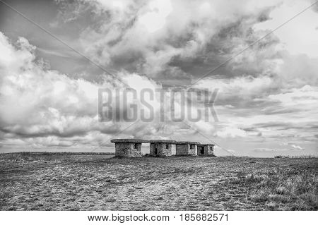 small stony building or little empty houses in field with grass and cloudy sky outdoor on natural background black and white