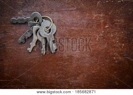 A bunch of the old metal grey small key on old grunge wooden surface with copy space