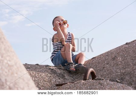 smiling little boy with half removed sunglasses and sailor shirt looking at the sky sitting on concrete breakwater