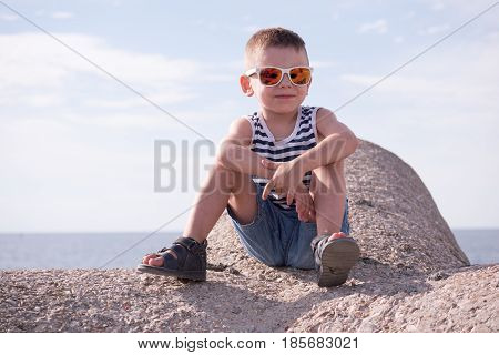 smiling little boy with sunglasses vest and shorts sitting on breakwater in front of sky and sea