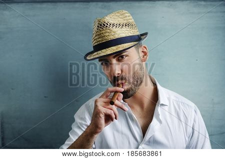 Young man with modern hat smoking a cuban cigar in front of blue wall