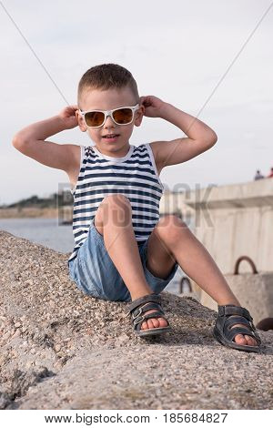 Beautiful little boy in sunglasses and sailor vest and shorts sitting on breakwater on background of pier and sea touching his sunglasses