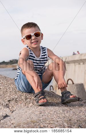 adorable smiling boy in sunglasses sitting on concrete breakwater in the port