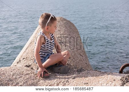 cute little boy with sunglasses sits on a breakwater on the background of the sea looking away
