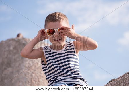 Cute smiling little boy in sunglasses and a vest sitting on a concrete breakwater on blue sky background closing one eye with his hand