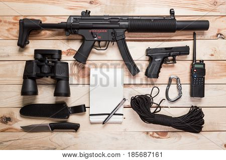 Assault rifle gun knife with sheath compass and notebook with pen on table.