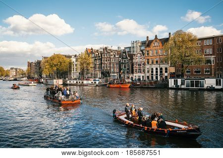 Amsterdam Netherlands - 27 April 2017: : Local people and tourists dressed in orange clothes ride on boats and participate in celebrating King's Day along the canal of Amsterdam.