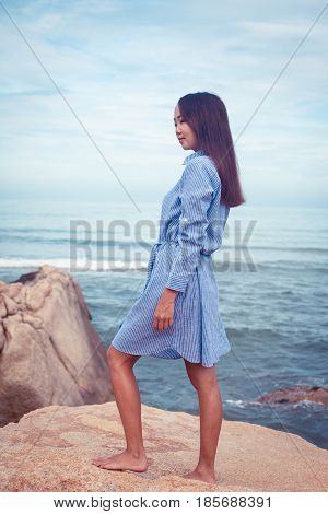 A portrait of beautiful asian woman in blue dress back stand on a stone by the sea