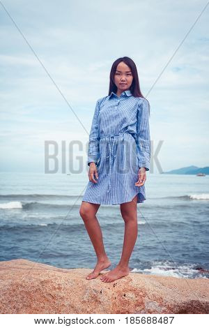 A portrait of beautiful asian woman in blue dress stand on a stone by the sea