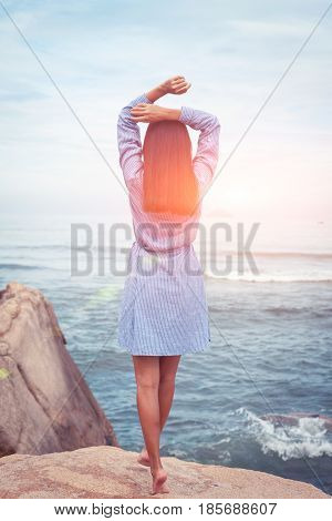 A sunny portrait of beautiful asian woman in blue dress back stand and rise hands on a stone by the sea