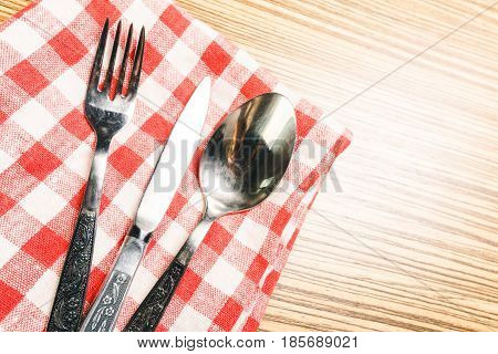 Fork and table knife on red gingham tablecloth