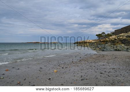 Coastal beach in Cohasset Massachusetts with the ocean lapping the shore.