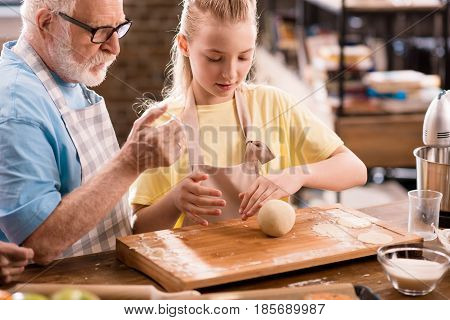 grandfather and granddaughter cooking and kneading dough for cookies at kitchen table cooking in kitchen concept