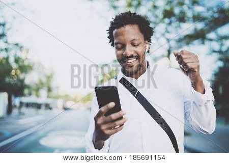 Portrait of Smiling African American man in headphones standidng in sunny street enjoying to music on his smart phone.Concept of guy using Internet-enabled electronic device, texting friends.Blurred
