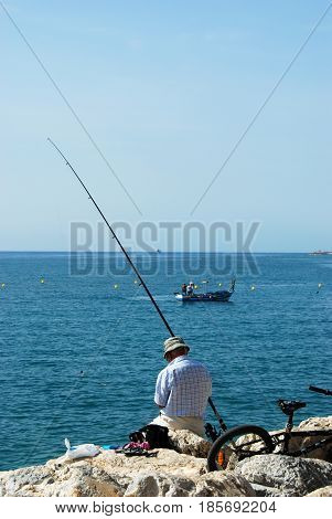 TORREMOLINOS, SPAIN - SEPTEMBER 3, 2008 - Man fishing from the breakwater with views towards the sea Torremolinos Malaga Province Andalusia Spain Western Europe, September 3, 2008.