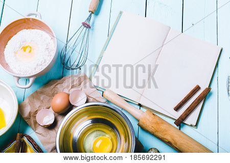 Preparation of the dough. Ingredients for the dough - Eggs and flour with a rolling pin. On wooden background.