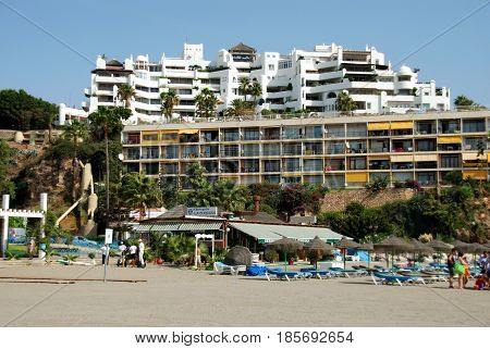 TORREMOLINOS, SPAIN - SEPTEMBER 3, 2008 - Tourists relaxing on the beach with apartments to the rear Torremolinos Malaga Province Andalusia Spain Western Europe, September 3, 2008.