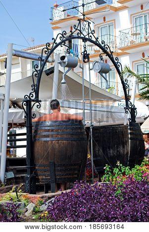 TORREMOLINOS, SPAIN - SEPTEMBER 3, 2008 - Man taking a shower in a barrel beach shower outside beach bar Torremolinos Malaga Province Andalusia Spain Western Europe, September 3, 2008.