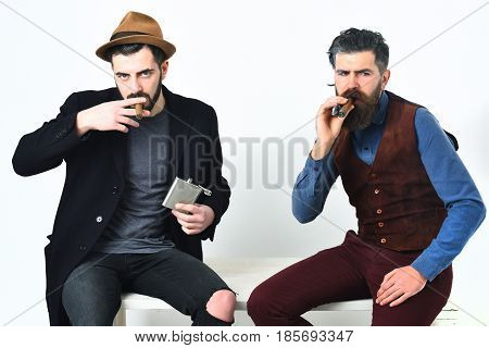 Two bearded mens short and long beard. Caucasian stylish hipsters with moustache holding flask with alcohol drink and smoking cigar isolated on white background