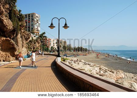 TORREMOLINOS, SPAIN - SEPTEMBER 3, 2008 - Tourists relaxing on the beach and promenade Torremolinos Malaga Province Andalusia Spain Western Europe, September 3, 2008.