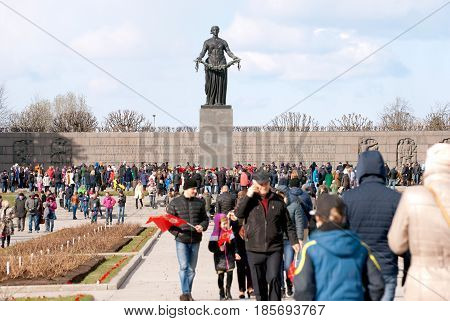 SAINT-PETERSBURG, RUSSIA, MAY 9, 2017: Crowd of people with flags and flowers on Piskaryovskoye Memorial Cemetery near Mother Motherland Sculpture on Victory Day of the Great Patriotic War 1941-1945