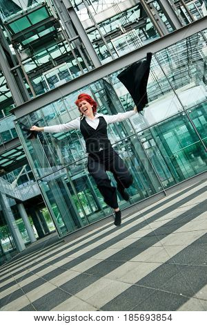 businesswoman jumping in front of an office building.