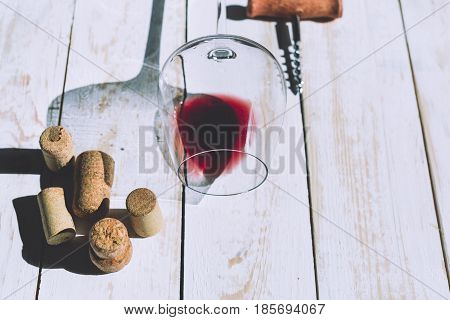 Wine glass cork and corkscrew over wooden table