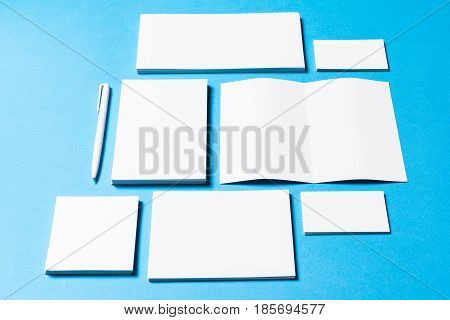 blank office objects organized for company presentation on blue paper background