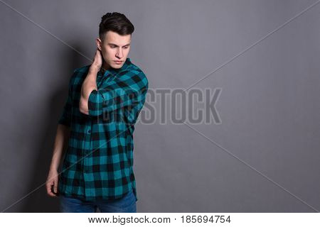 Handsome man model studio portrait. Boy casual style, trendy hipster in checkered shirt look with cool hairstyle