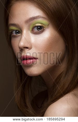 Beautiful red-hair girl with creative green makeup. Beauty face. Photos shot in studio