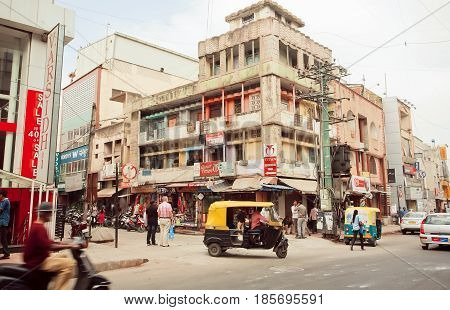 BANGALORE, INDIA - FEB 14, 2017: City transport with traditional indian auto-rickshaw on street with shops on February 14, 2017. With population 8.52 million Bangalore is 3-rd most populous indian city