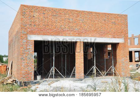 Building new brick wall garage for two cars with formwork for ceiling inside.