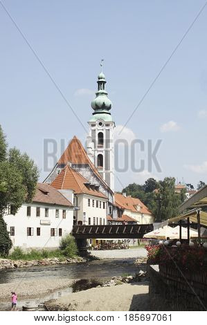 St. Jost Church by the river in Cesky Krumlov Czech Republic during summer with people enjoying the cool water in the river.