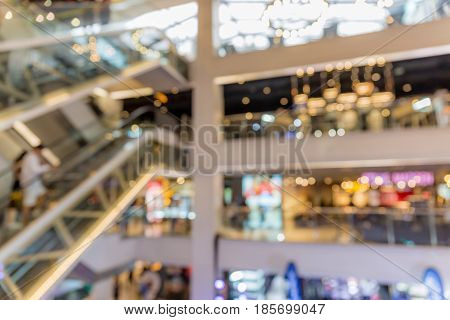 Abstract blurred photo of people on escalators in shopping department store.