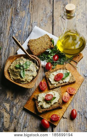 Mediterranean cuisine recipe. Hummus and baba ganush with homemade bread slices and cherytomatos on wooden table.