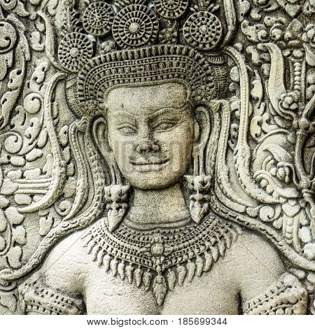 Close up of face of a stone carving of an angel or Apsara on the wall of Angkor Wat the ancient Hindu temple complex in Cambodia