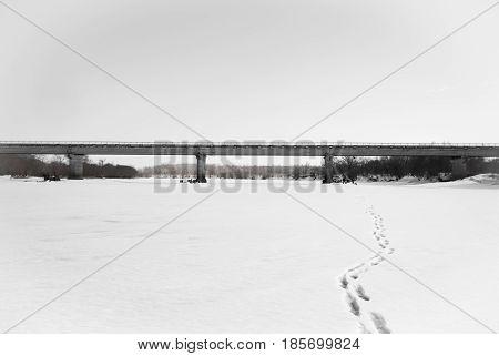 Concrete bridge over the frozen river .