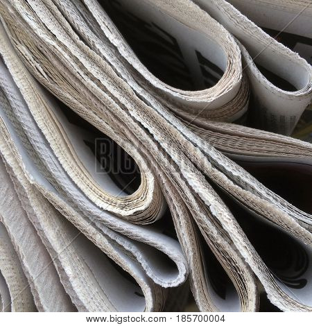 Close up of the edges of a stack of folded newspapers