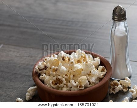 Popcorn In A Bowl With Salt On A Wooden Background