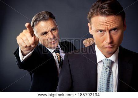studio shot of a senior businessman firing a younger employee