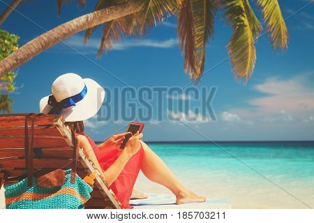 woman with touch pad on tropical beach vacation