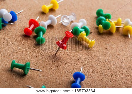 Group of thumbtacks pinned on corkboard. close up