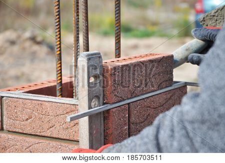 Bricklayer Worker Installing Red Clinker Blocks and Caulking Brick Masonry Joints Exterior Wall with Trowel putty Knife and Fixing with Spirit Level.