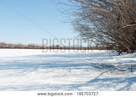 Winter landscape with frozen river . .